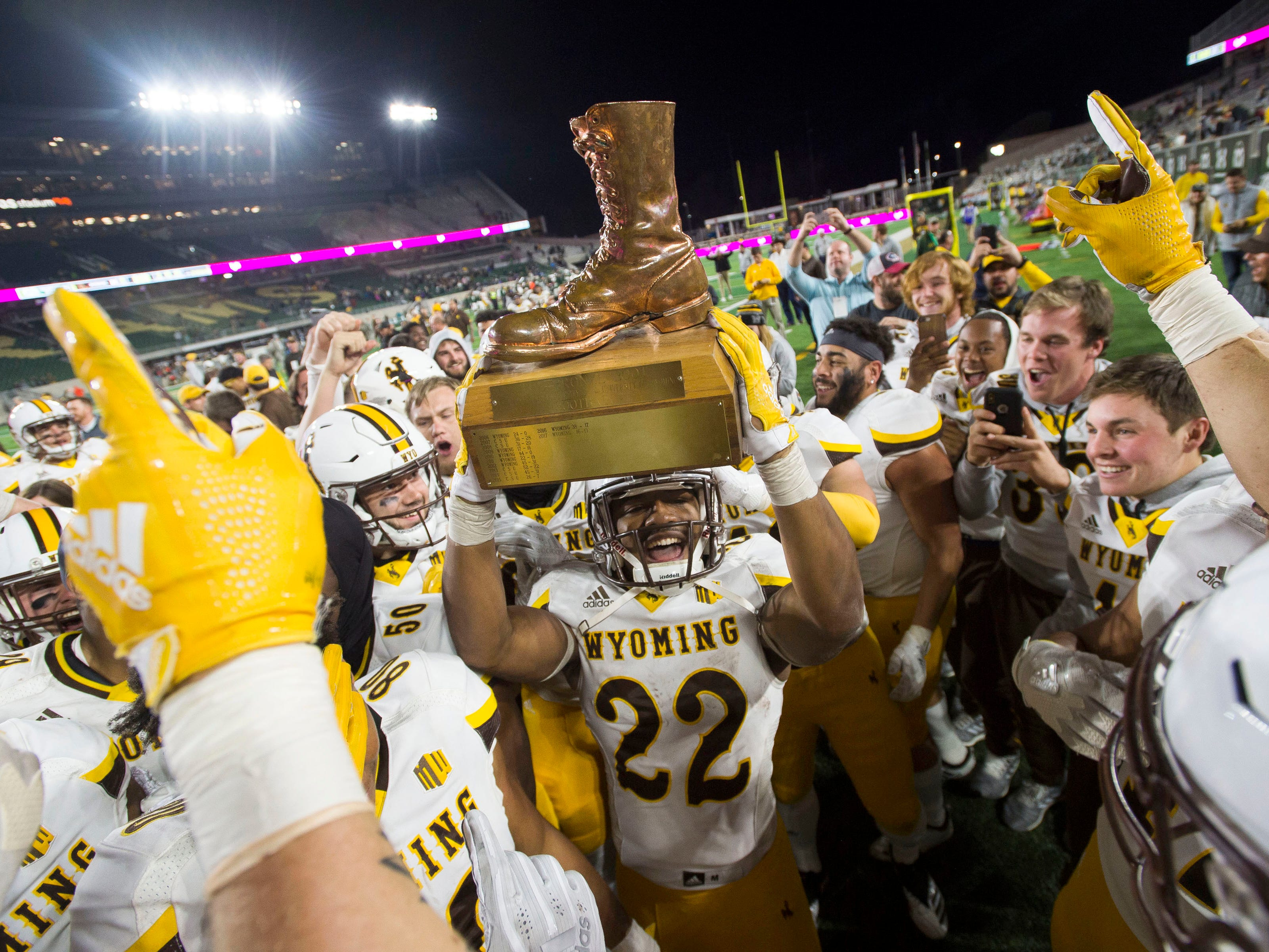 Bronze Boot: Wyoming running back Nico Evans hoists up the Bronze Boot trophy after Wyoming defeated Colorado State, 34-21, to retain the award at Canvas Stadium in Fort Collins, Colo. on Oct. 26.