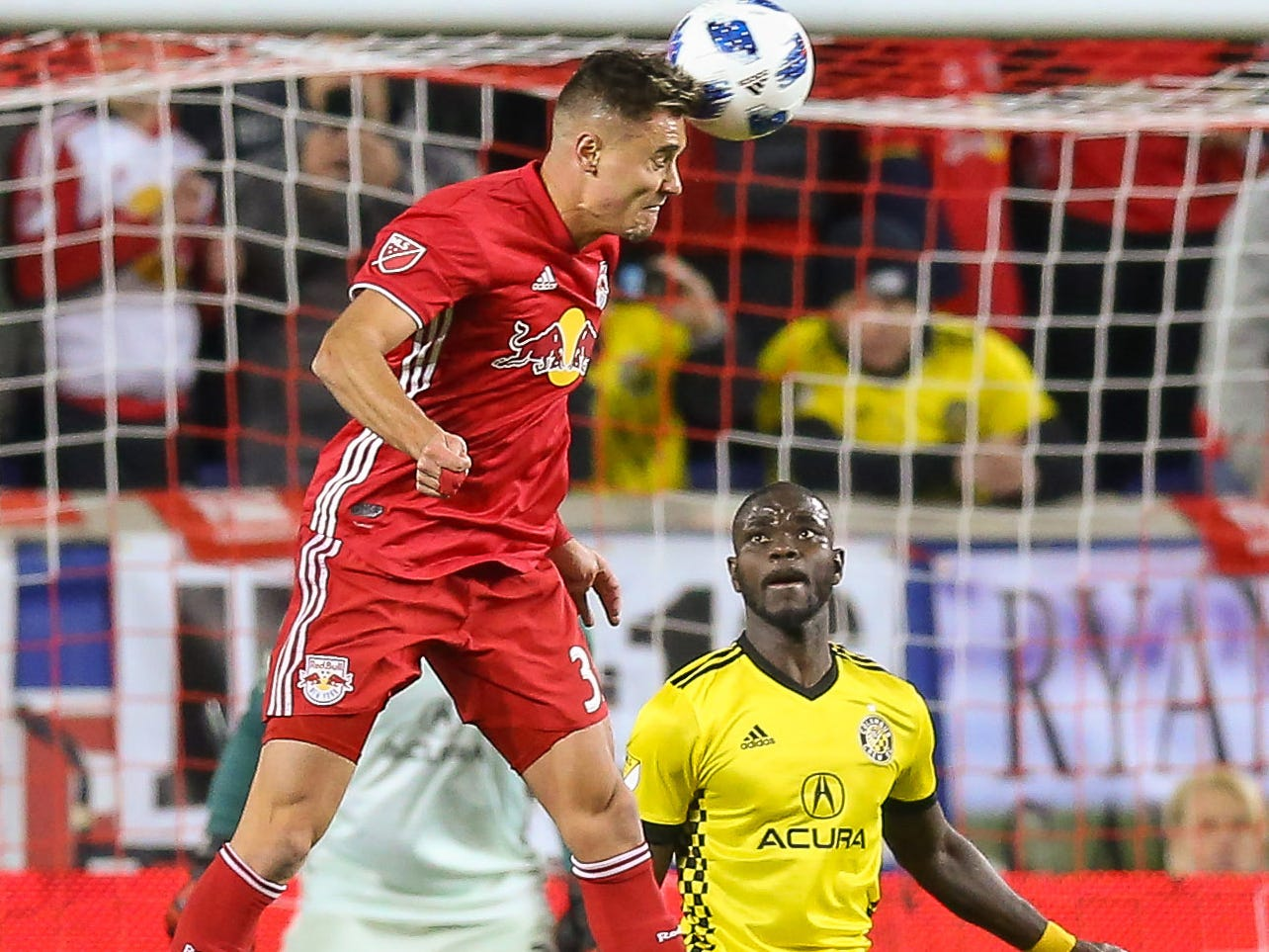 New York Red Bulls midfielder Aaron Long (33) heads the ball toward goal as Columbus Crew defender Jonathan Mensah defends during the first half in the Eastern Conference semifinal at Red Bull Arena. NYRB won the game, 3-0, to advance to the Eastern Conference final.