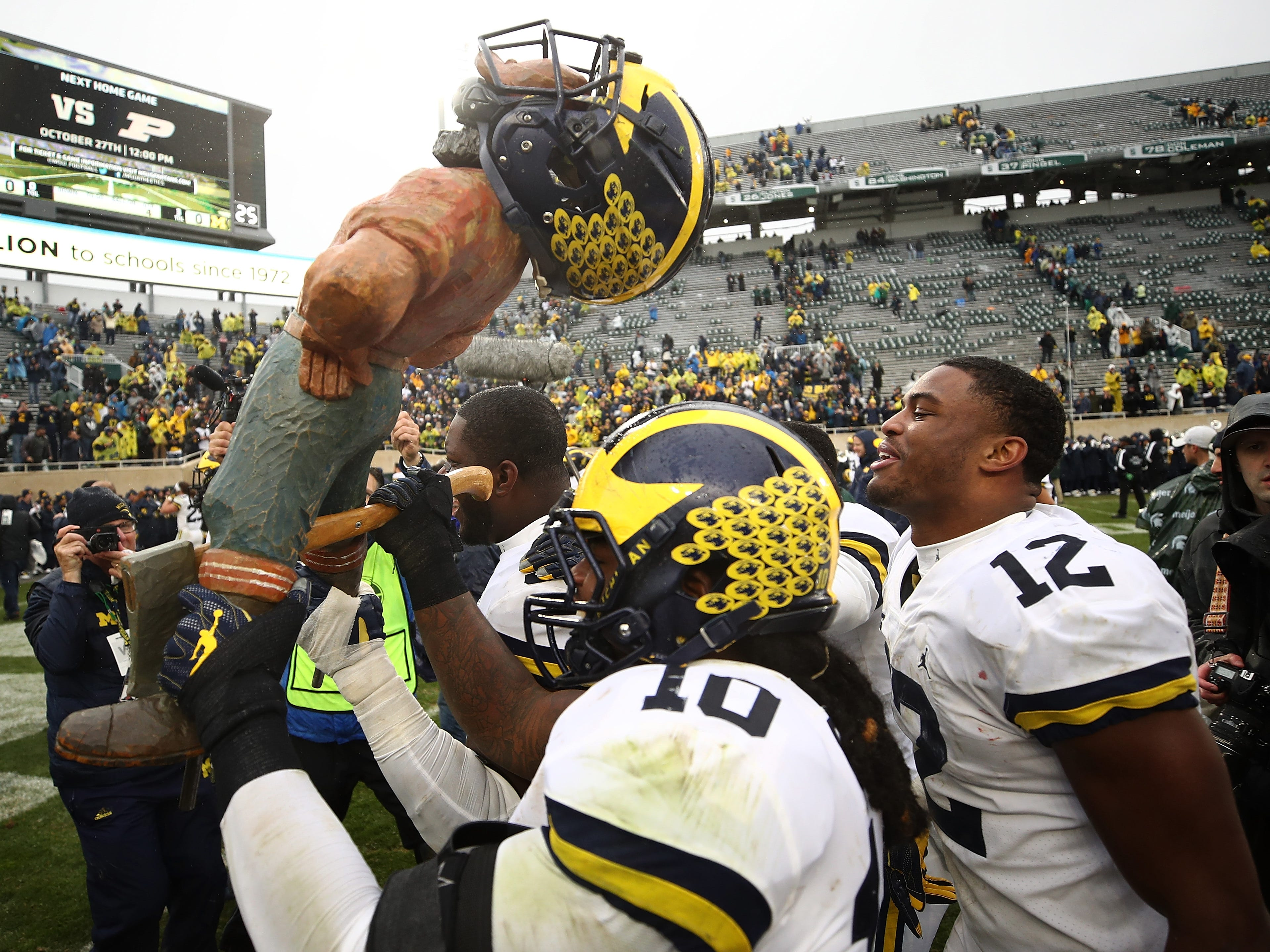 Paul Bunyan Trophy: Michigan players carry the Paul Bunyan Trophy off the field after beating Michigan State, 21-7, at Spartan Stadium on Oct. 20.