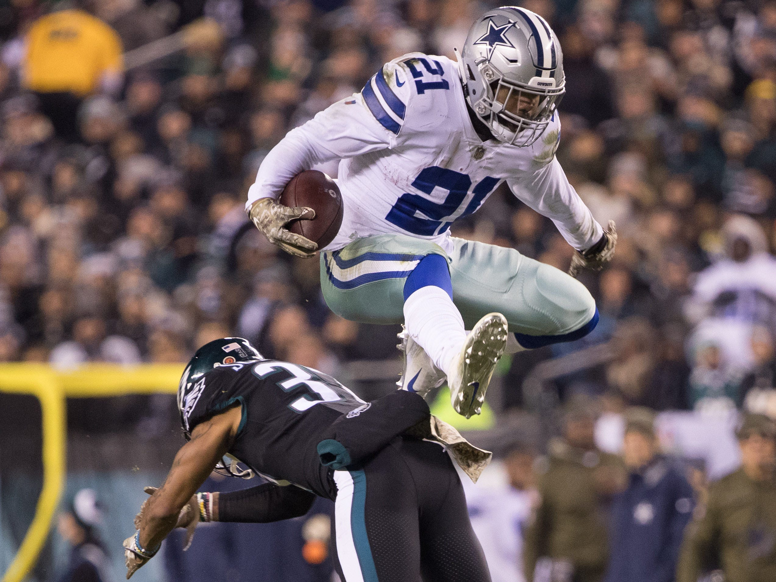 Dallas Cowboys running back Ezekiel Elliott leaps over the tackle attempt of Philadelphia Eagles defensive back Tre Sullivan during the second quarter at Lincoln Financial Field.