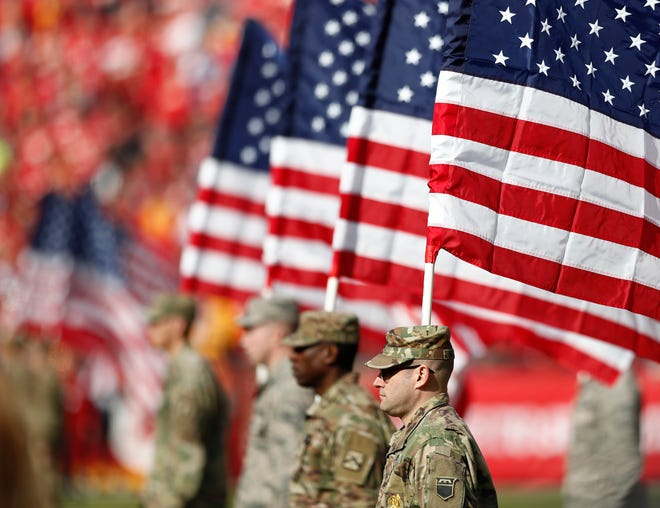 Members of the United States military hold American flags on the field during the National Anthem on Veterans Day before the Arizona Cardinals game against the Kansas City Chiefs at their NFL football game at Arrowhead Stadium in Kansas City, Missouri.