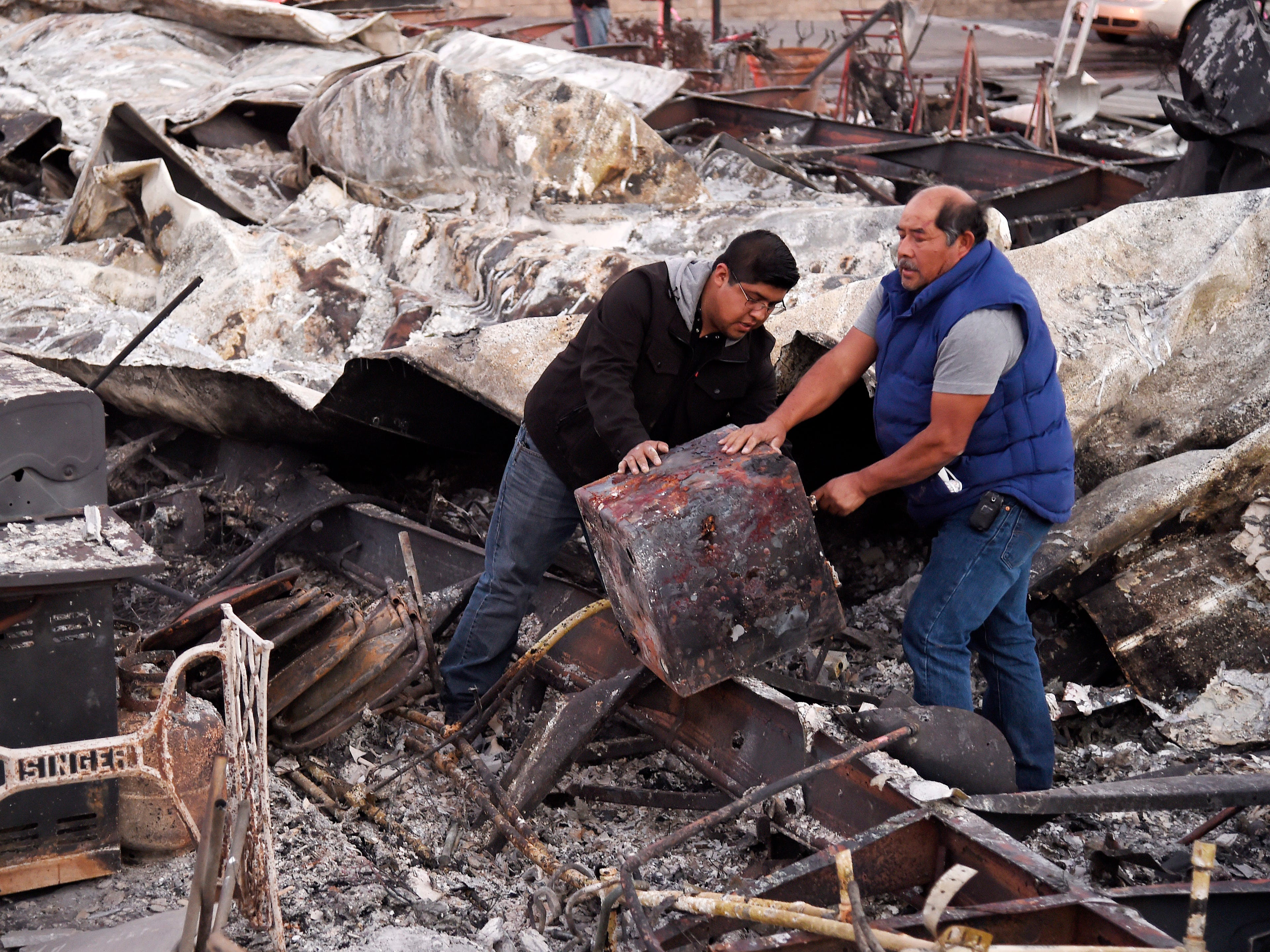 Santos Alvarado, right, and his son Ricky recover a safe from their destroyed home at Seminole Springs Mobile Home Park on Nov. 11, 2018, following devastating wildfires in the area in Agoura Hills, Calif.