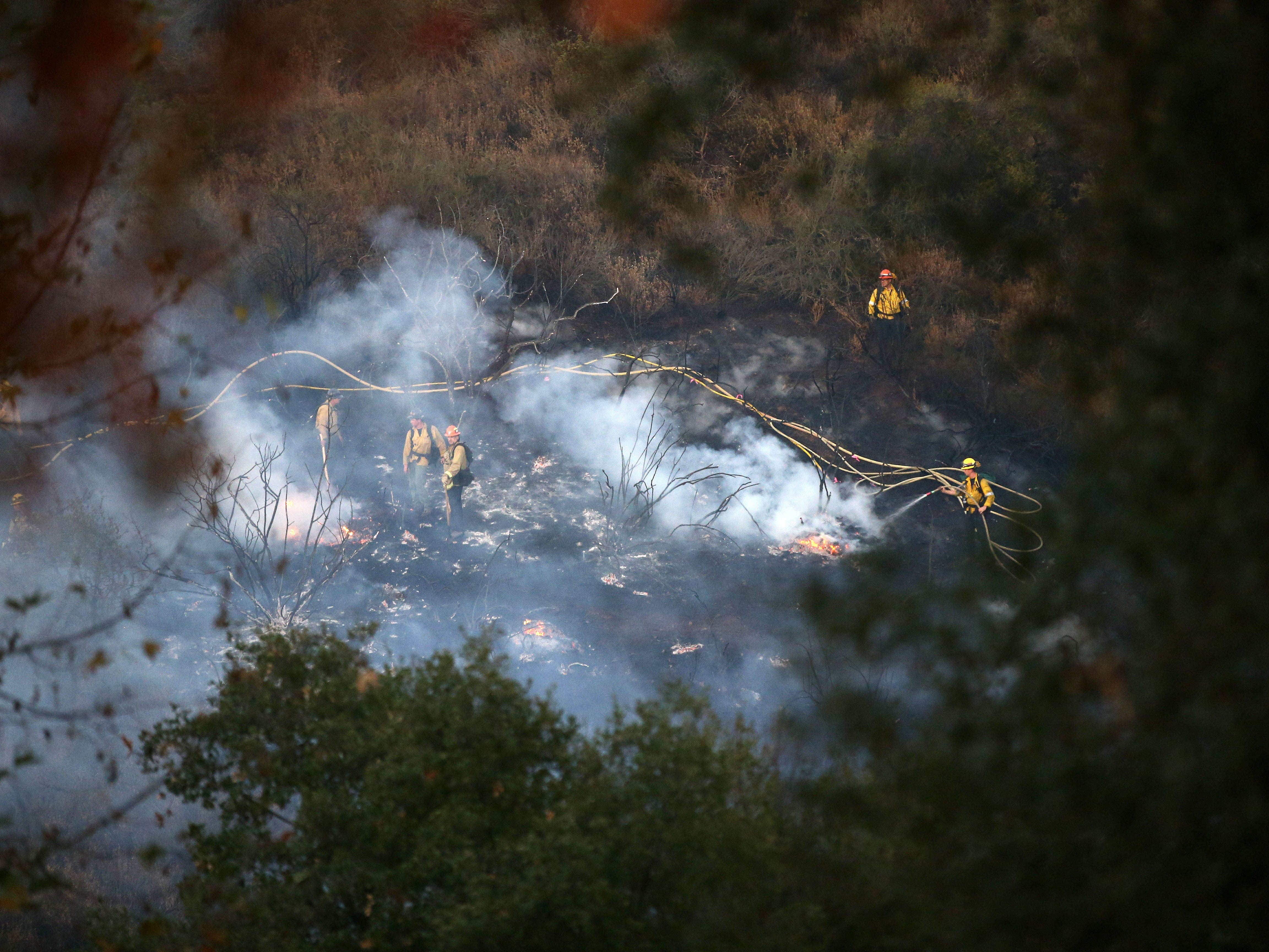 Firefighters from Glendale, Calif. battle flames from the Woolsey Fire on Nov. 11, 2018, in Westlake Village, Calif.