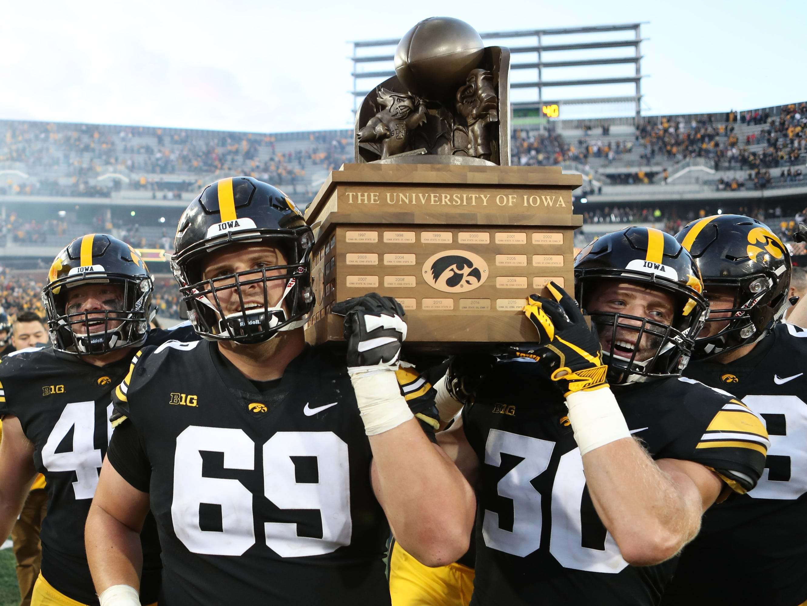 Cy-Hawk Trophy: Iowa Hawkeyes offensive lineman Keegan Render (69) and Idefensive back Jake Gervase (30) carry the Cy-Hawk trophy off the field after defeating Iowa State, 13-3,  at Kinnick Stadium on Sept. 8.
