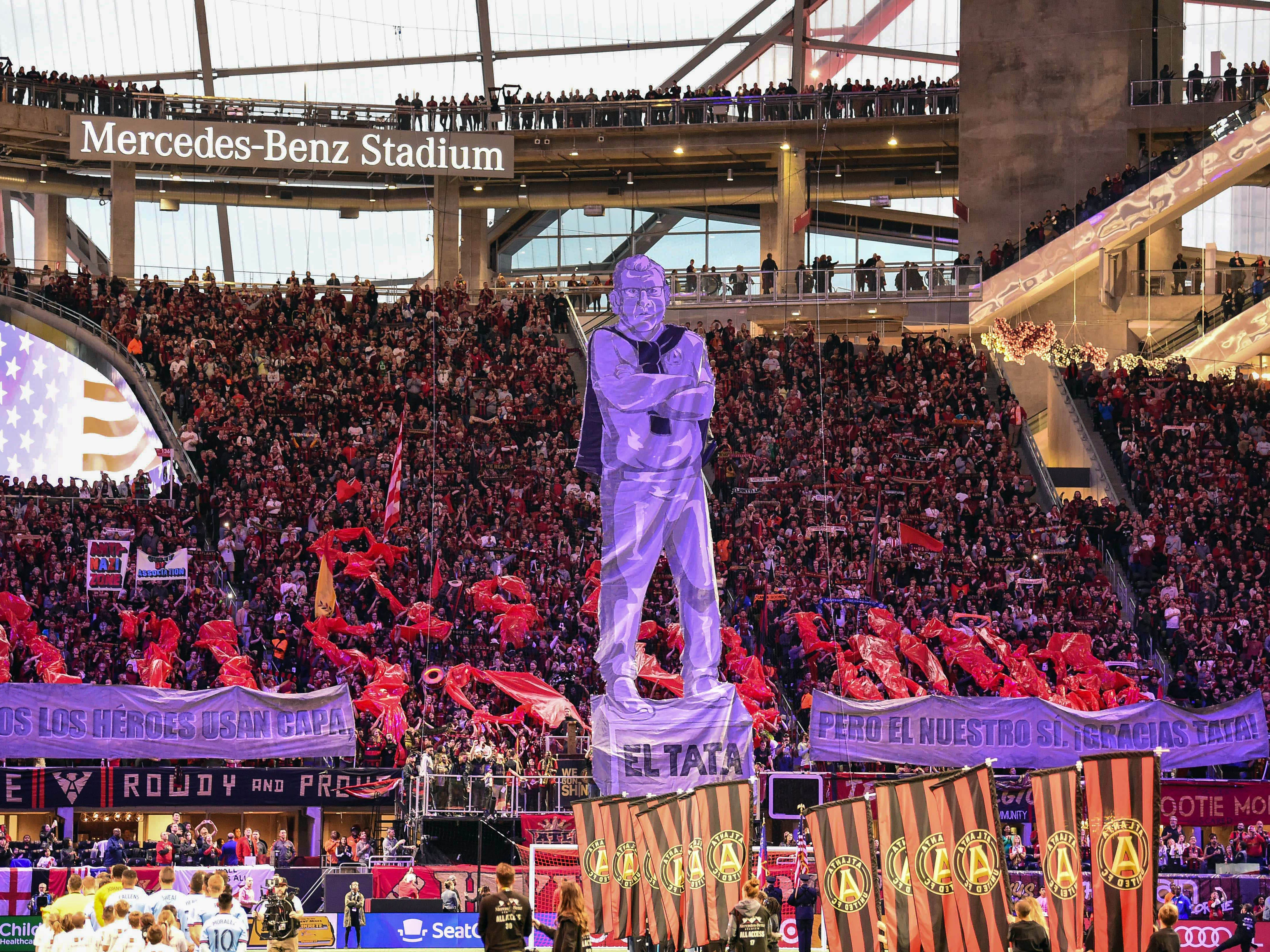 Atlanta United fans hoist a tifo of coach Gerardo Martino before the match against New York City FC in the Eastern Conference semifinal at Mercedes-Benz Stadium.
