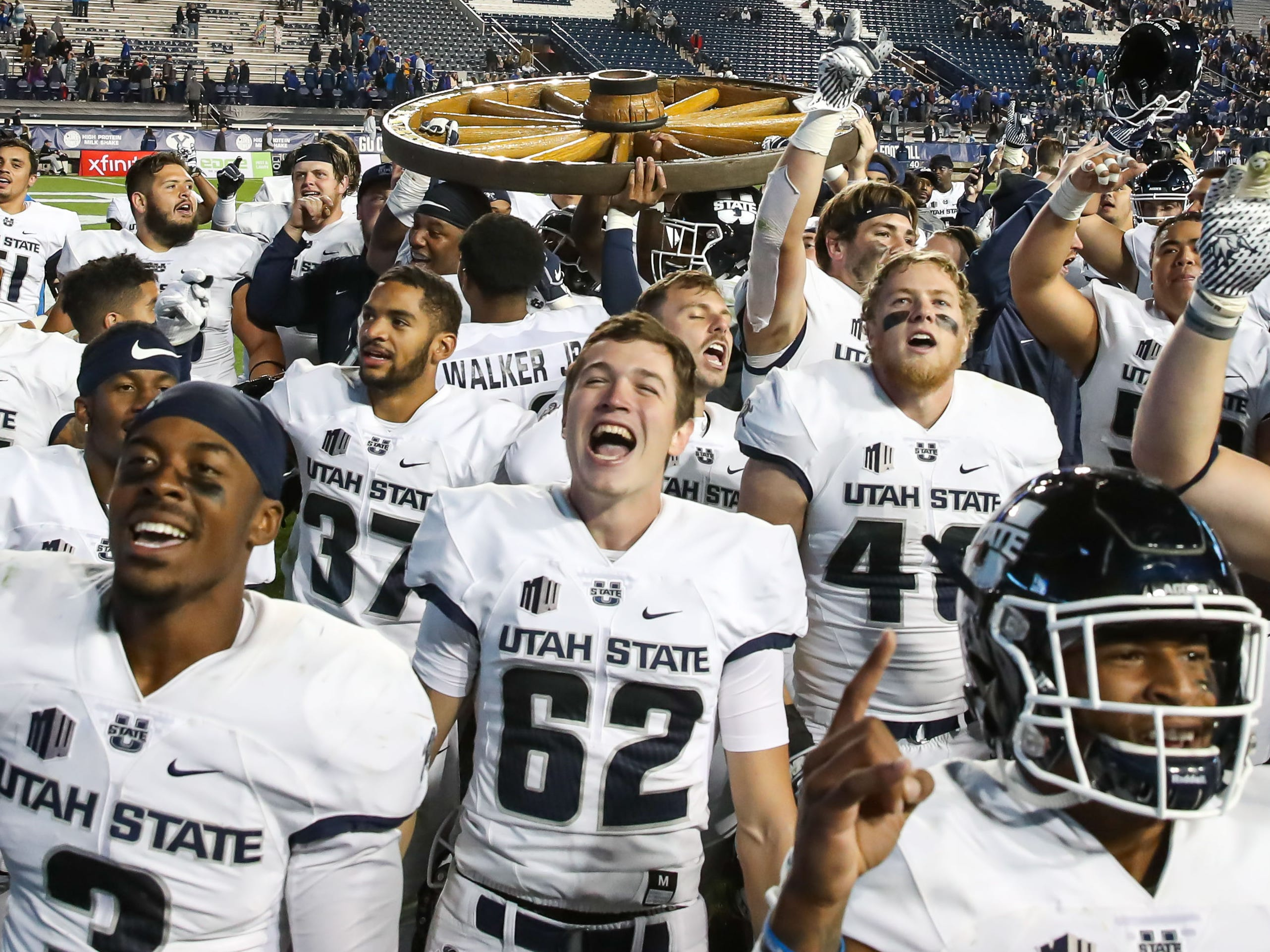 Old Wagon Wheel: Utah State players celebrate after a 45-20 win over BYU  at LaVell Edwards Stadium on Oct. 5.