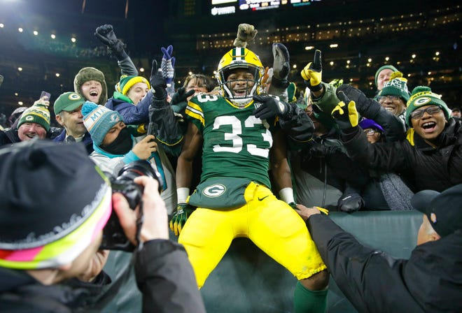 Green Bay Packers running back Aaron Jones celebrates a touchdown with the Lambeau Leap during the third quarter against the Miami Dolphins.