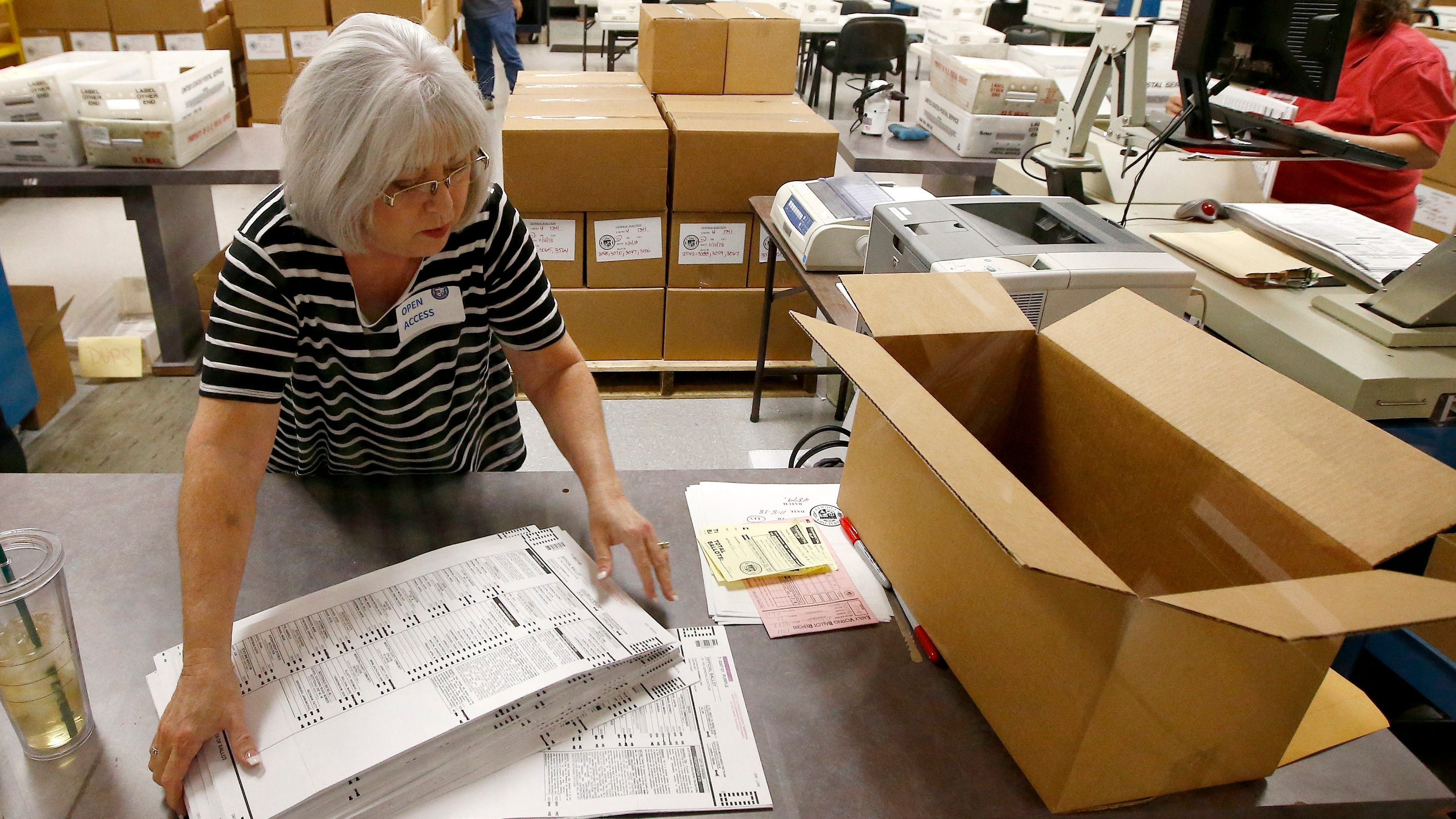 Workers at the Maricopa County Recorder's Office go through ballots Thursday, Nov. 8, 2018, in Phoenix. There are several races too close to call in Arizona, especially the Senate race between Democratic candidate Kyrsten Sinema and Republican candidate Martha McSally.\