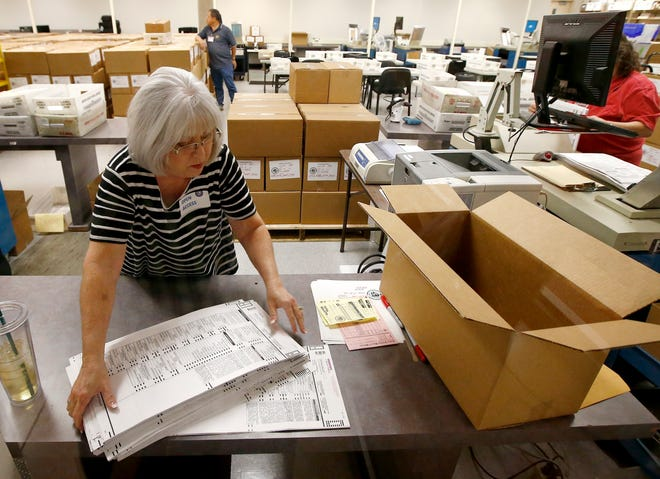 Workers at the Maricopa County Recorder's Office go through ballots Nov. 8, 2018, in Phoenix.