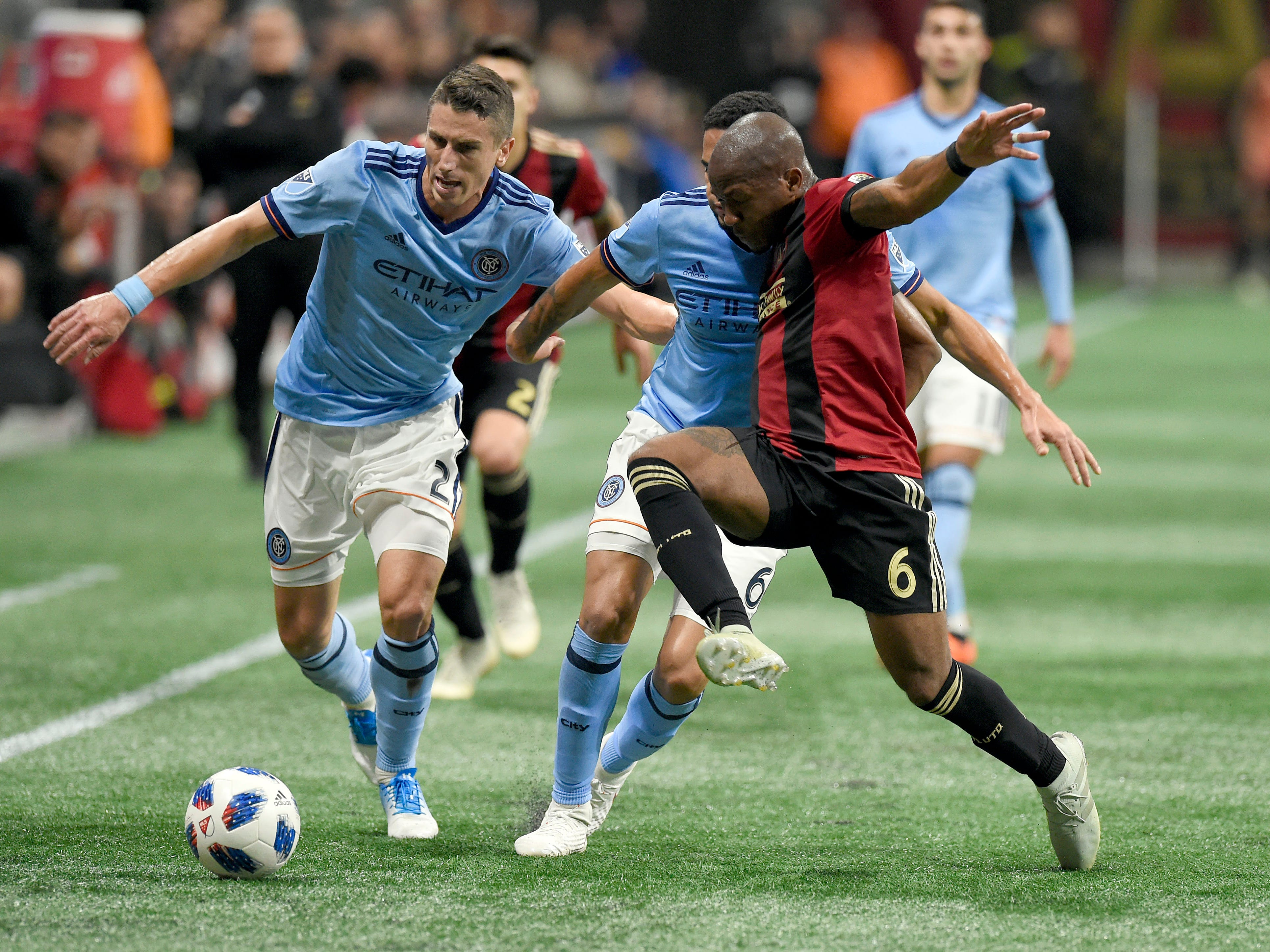 New York City FC defender Ben Sweat (2) battles for the ball with Atlanta United midfielder Darlington Nagbe (6) during the second half of the Eastern Conference semifinal at Mercedes-Benz Stadium.