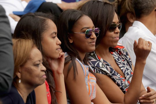 (L-R) Marian Robinson, Malia Obama, Sasha Obama, and First Lady Michelle Obama attend an exhibition of Cuban national baseball team and enemies in Tampa Bay, Havana, Cuba on March 22, 2016.