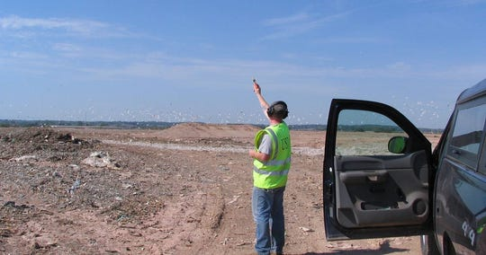 A Wildlife Services employee shoots a pyrotechnic from a handheld launcher to disperse the gulls at the Outagamie County landfill.