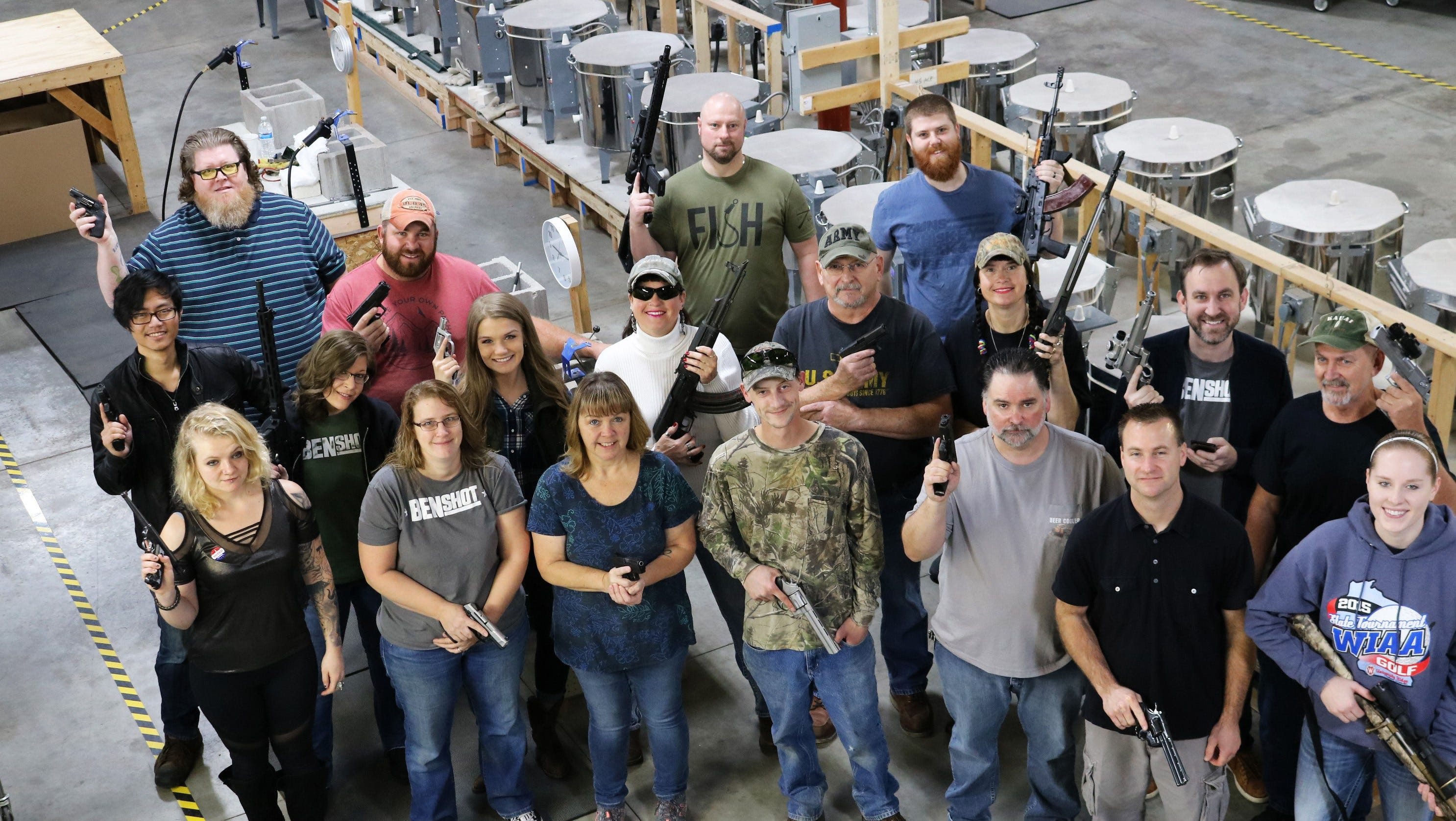 Employees at BenShot, a business that produces glassware embedded with bullets, show off their guns at their workshop in Hortonville. Each employee was given a handgun as a Christmas gift from the business.