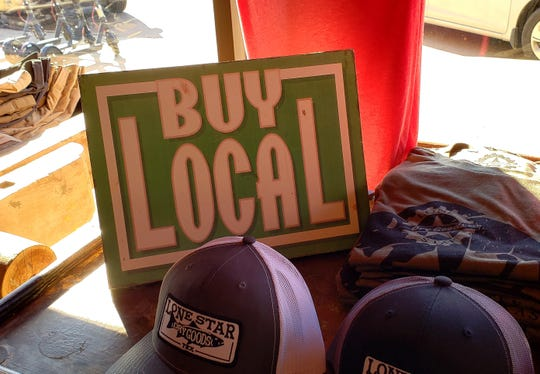 "A ""Buy Local"" sign inside Lone Star Dry Goods' front window in downtown Abilene."