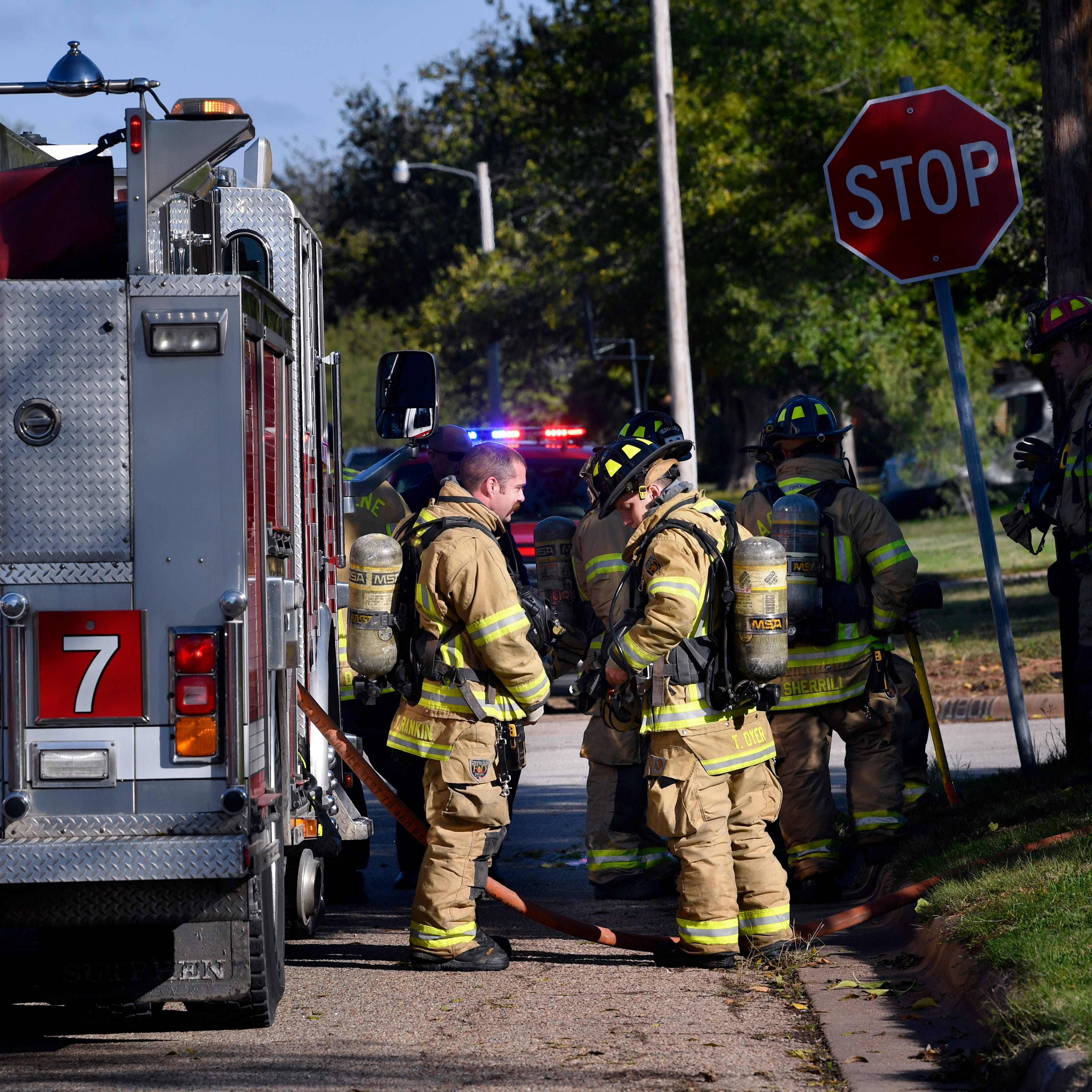 Abilene firefighters stand beside a fire truck after responding to a fire in the 1700 block of Glenhaven Drive Tuesday Nov. 13, 2018. Four occupants of the home were transported to a local hospital.
