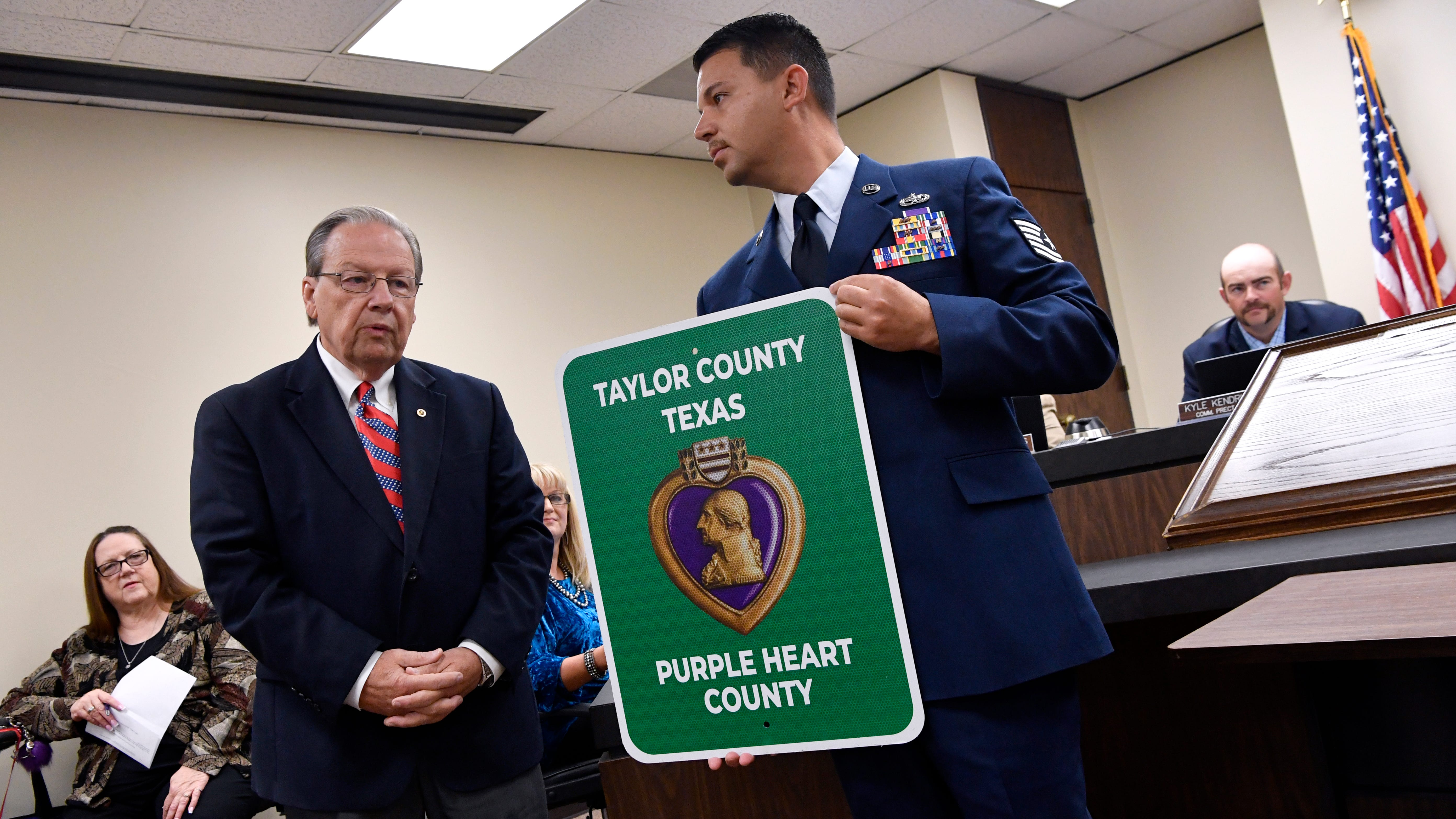 Air Force Tsgt. Jesus Soto, the commander of Chapter #1937 of the Military Order of the Purple Heart, stands beside Taylor County Judge Downing Bolls after the county's designation as a Purple Heart County during Tuesday's meeting of the commissioners court Nov. 13, 2018.