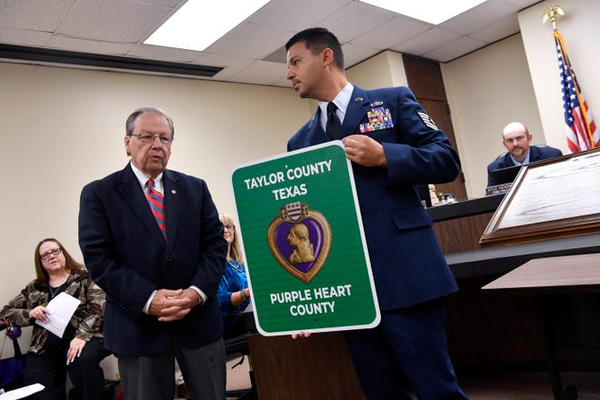 """TSgt. Jesus Soto, commander of Chapter No. 1937 of the Military Order of the Purple Heart, stands beside Taylor County Judge Downing Bolls after the county's designation as a Purple Heart County during Tuesday's meeting of the Commissioners Court.  According to the website purpleheart.org, Purple Heart counties and cities are part of the Purple Heart Trail that """"creates a symbolic and honorary system of roads, highways, bridges and other monuments giving tribute to the men and women who have been awarded the Purple Heart medal."""""""