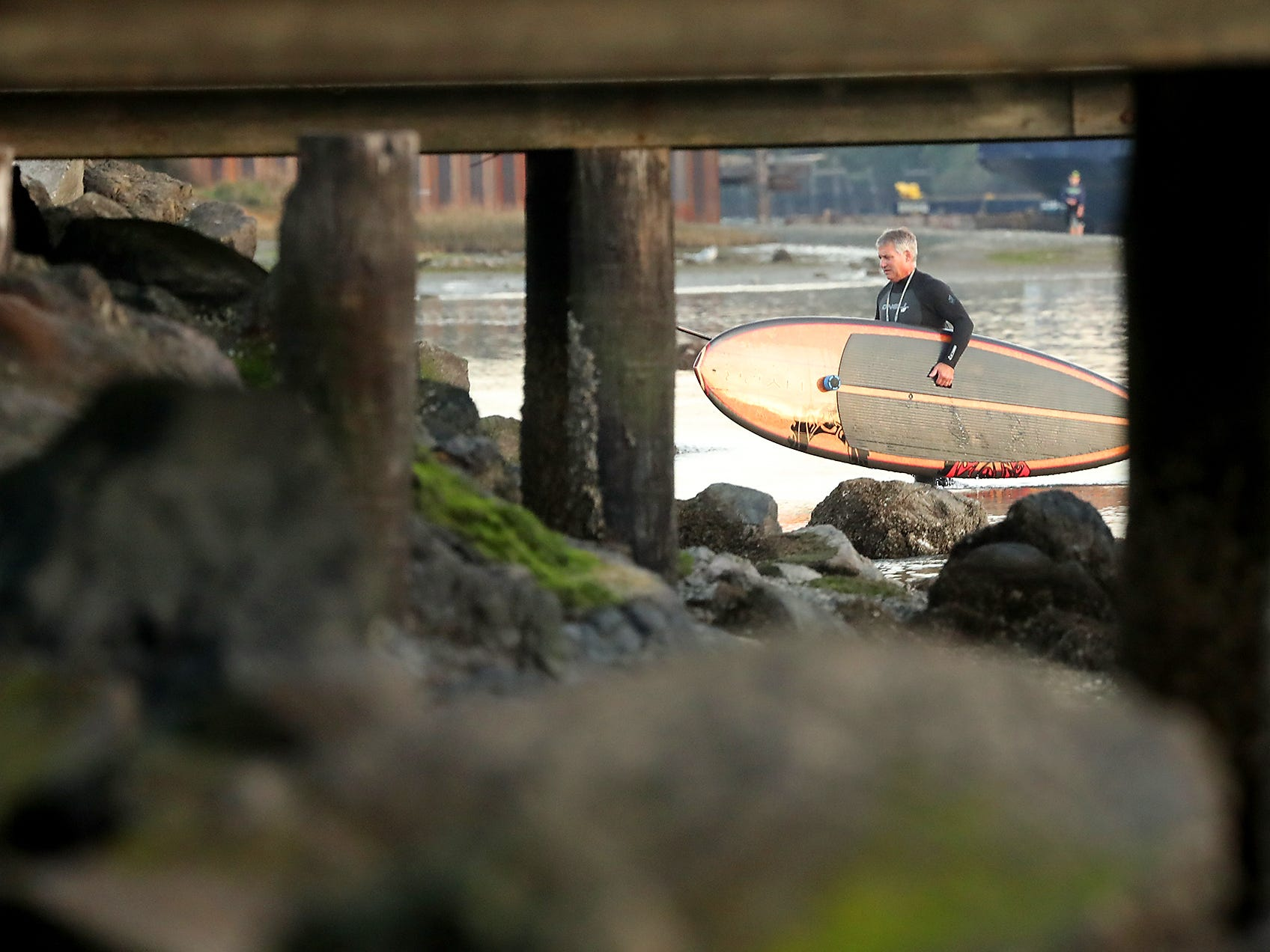 Mark Jeffries, of Bremerton, is framed by the dock pilings as he carries his stand-up paddle board out of the water after paddling at Lions Park in Bremerton on Monday, November 12, 2018.