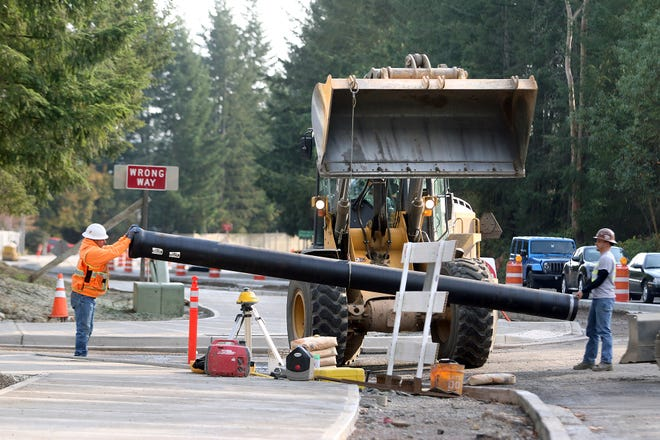 Nordland Construction workers Robert Massey, left, and Jobey Hathaway move an iron drain pipe at Ridgetop's intersection at Quail Run on Tuesday. The intersection will contain a roundabout when work is complete.