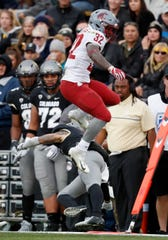 Washington State running back James Williams hurdles Colorado defensive back Dante Wigley during the Cougars' win Saturday in Boulder. Williams has rushed for 437 yards and nine touchdowns and has a team-high 63 receptions for 506 yards and another three touchdowns.