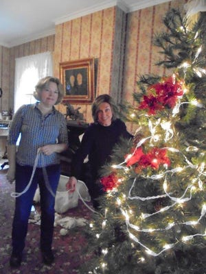 Kim Beckley and Sarah Kalbof the Earth, Wind and Flowers Garden Club tackle the parlor treeat the Bucyrus Historical Society.This season, lights have been added to all threetrees.The emphasis on whitedecorations has been phased out with a return to traditional red color harmonies in decorations.