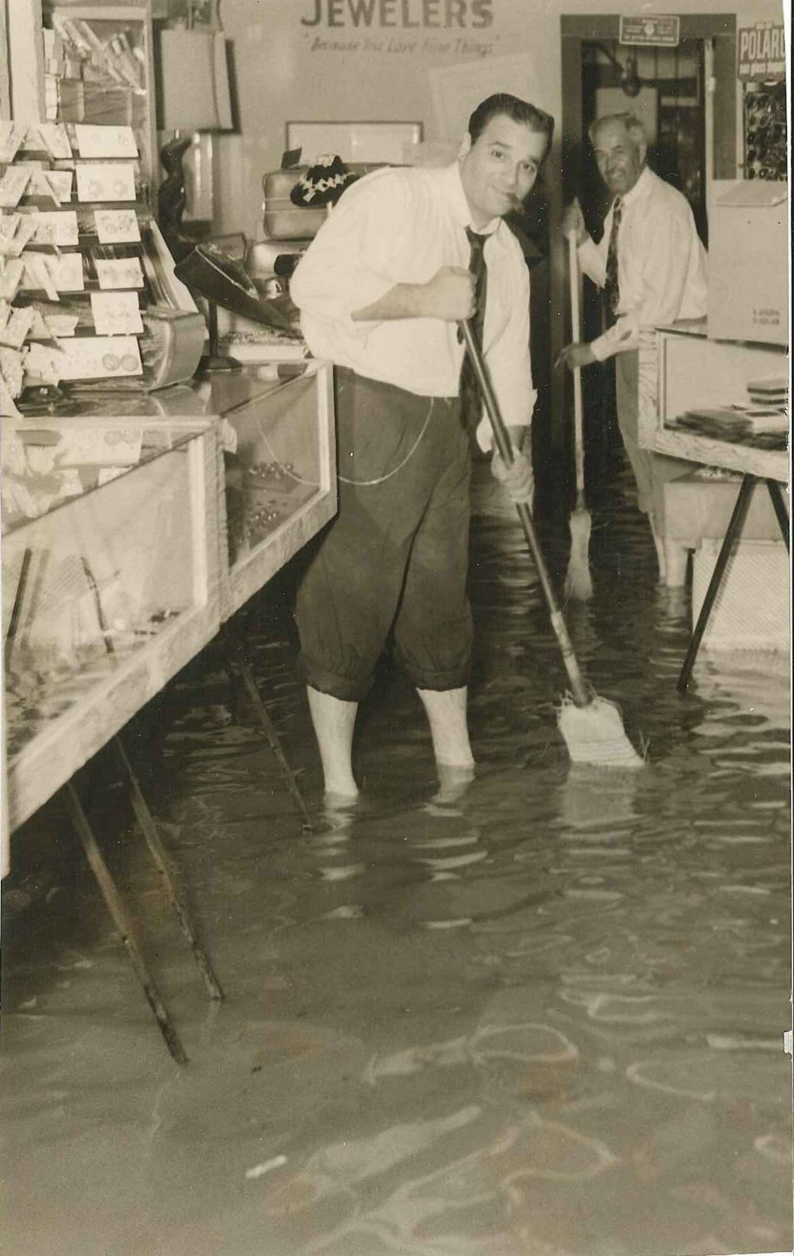 Joe Salem (foreground) and Henry Villasenor sweep water out of Salem's Jewelry Store at 310 North Chaparral in downtown Corpus Christi following heavy rainfall on April 24, 1956.