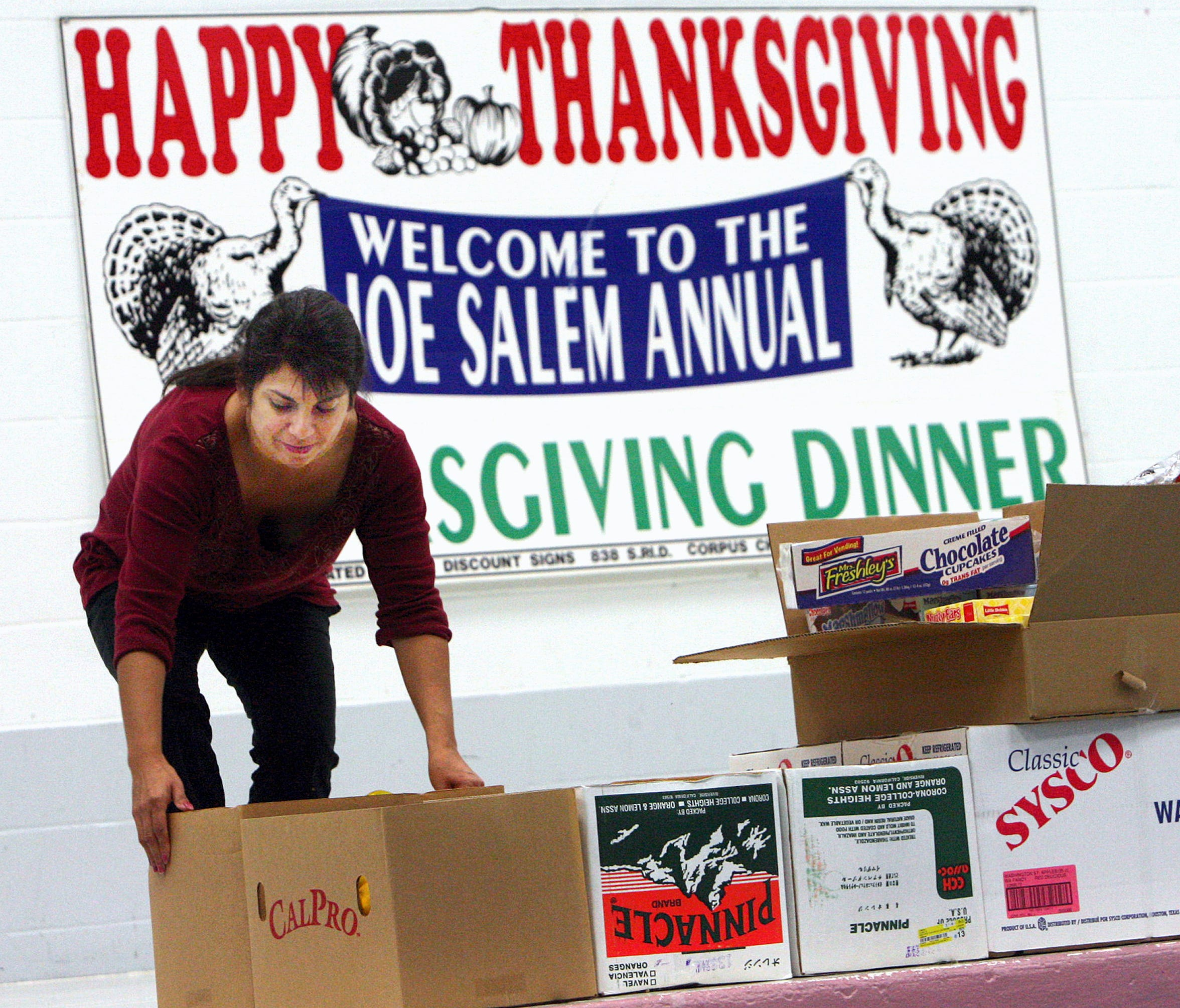 Gloria Martinez helps set up at the annual Joe Salem Thanksgiving Dinner. The annual community event celebrates its 75th anniversary on Thanksgiving Day.