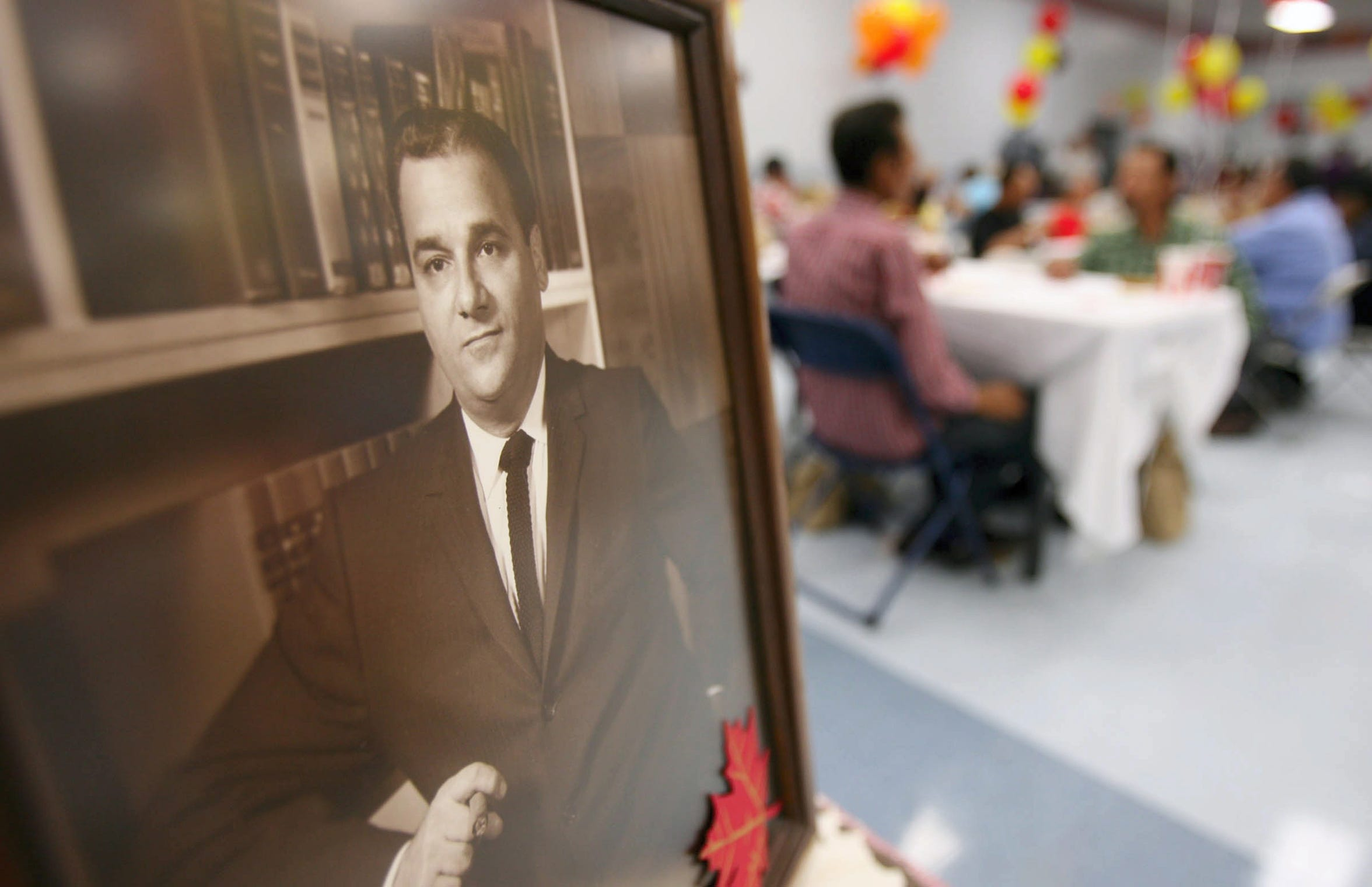 A portrait of Joe Salem watches over visitors and volunteers as they take part in the annual Thanksgiving dinner named in his honor Thursday, November 27, 2008 at the Greenwood Drive Boys and Girls Club of Corpus Christi.