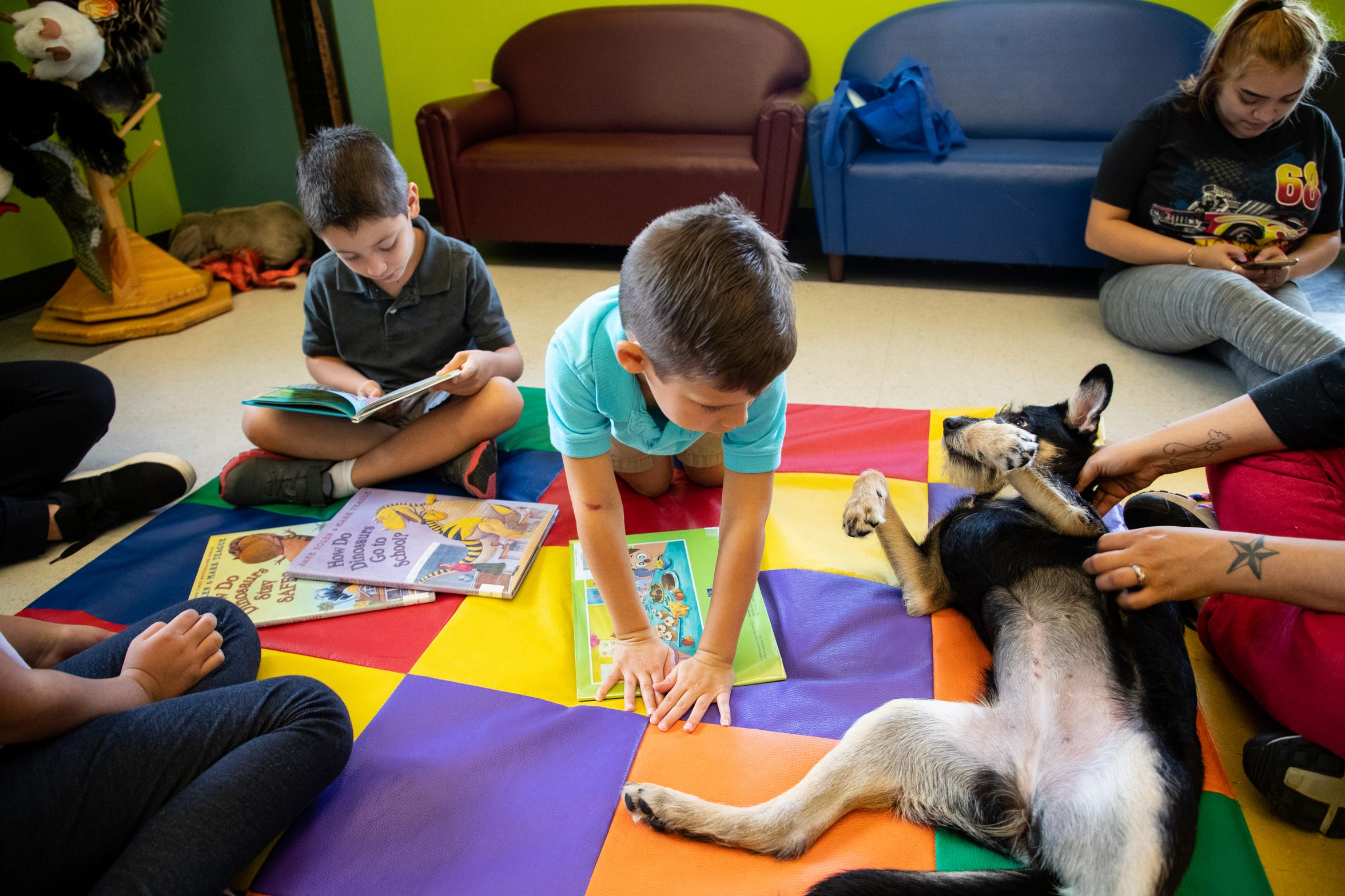 Bella the dog licks Josh Morgan as he flips through a children's book during a Read & Rollover event at Keach Family Library in Robstown on Wednesday, Nov. 7, 2018.