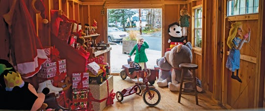 A little girl peers into Santa's Workshop during a past Dickens Days celebration in Clinton.