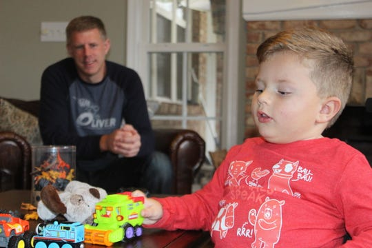 Oliver Schaper, who is receiving a first-of-its-kind treatment for spinal muscular atrophy, plays with his toys as his dad, Keith, looks on.