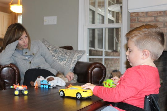 Oliver Schaper, who is receiving a first-of-its-kind treatment for spinal muscular atrophy, plays with his toys under the watchful eye of his mother, Misty.