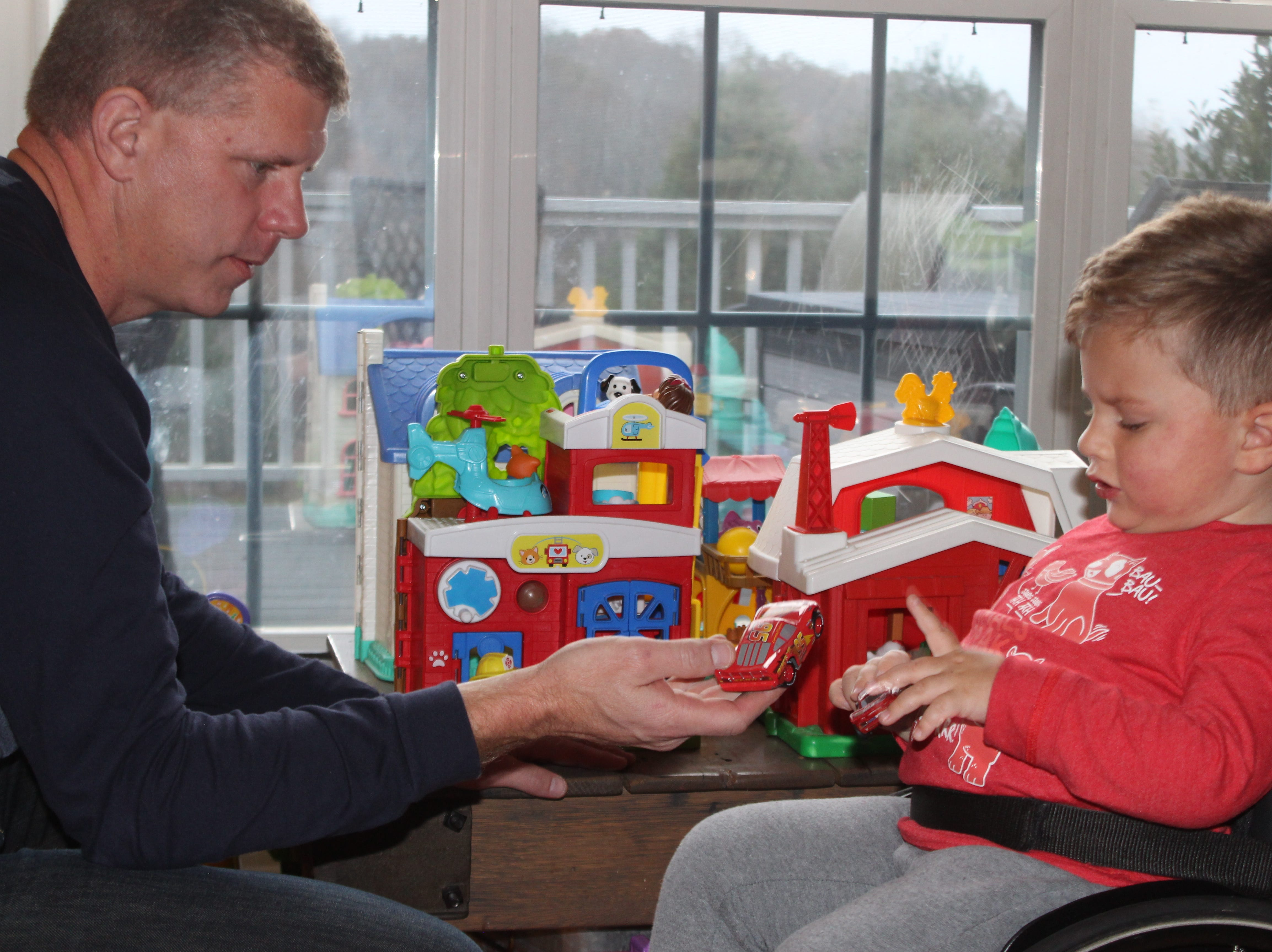 Oliver Schaper, who is receiving a first-of-its-kind treatment for spinal muscular atrophy, plays with his toy cars with his dad Keith.