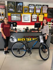 Miriam Gomez of Somerville Bike Shop (left) presents a bike to Kaitlyn Bedard of Empower Somerset (right), donated by Somerville Bike Shop as a grand prize for the tricky tray benefitting Empower Somerset and The Center School.