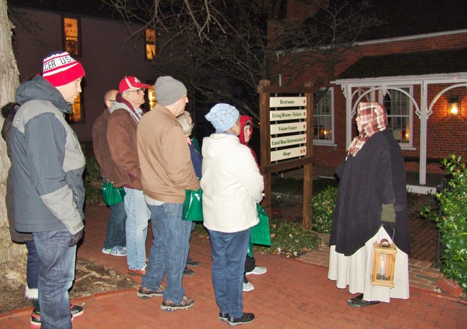 Living history interpreter Lasha Philabaum talks to visitors outside of the Toll House during a previous candlelight Roscoe Christmas tour.