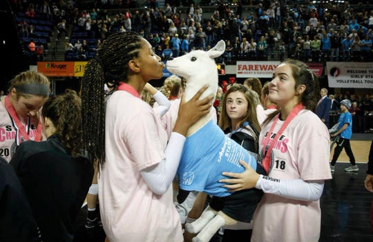 Ankeny Centennial's Devyn Robinson kisses the team's stuffed llama after the Jaguars' straight set sweep of Cedar Falls for the Class 5A state championship on Friday in Cedar Rapids.