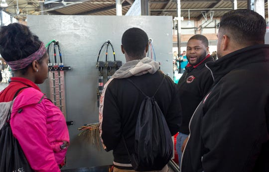 Motor City Electric Company Project Manager, Terrance Lewis, turns to a group of Detroit Collegiat Preparatory High School students during a demonstration at the Sachse Construction Academy in partnership with Junior Achievement, on Tuesday, Oct. 23, 2018 at Eastern Market in Detroit.  Over 500 Detroit high school students arrived at Eastern Market to learn about different companies and over 40 different skilled trades.
