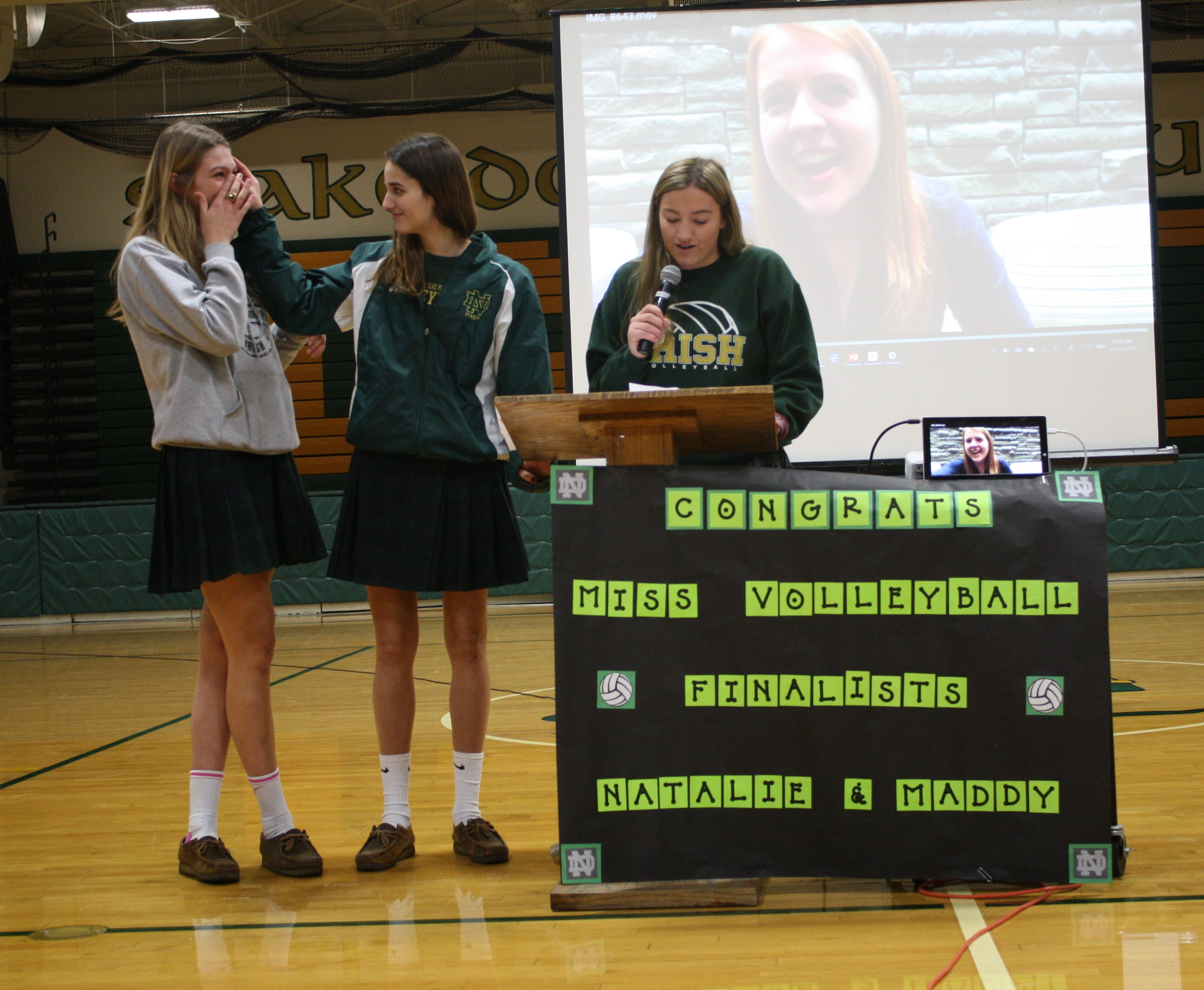 Natalie Risi (middle) wipes the tears of teammate Madeline Chinn (left), who was just announced as 2018 Michigan Miss Volleyball 2018 on Tuesday, Nov. 13, 2018, at Pontiac Notre Dame Prep. Fellow senior Maria Famularo is speaking at the podium.