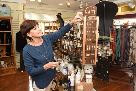 Terri Cooper, of Franklin Village Boutique, works in her store in the Franklin Village Plaza. Her business has been hurt by an ongoing public perception that the air inside her store isn't safe to breathe, as the plaza has had a recurrent vapor intrusion issue emerging from buried underground solvents.