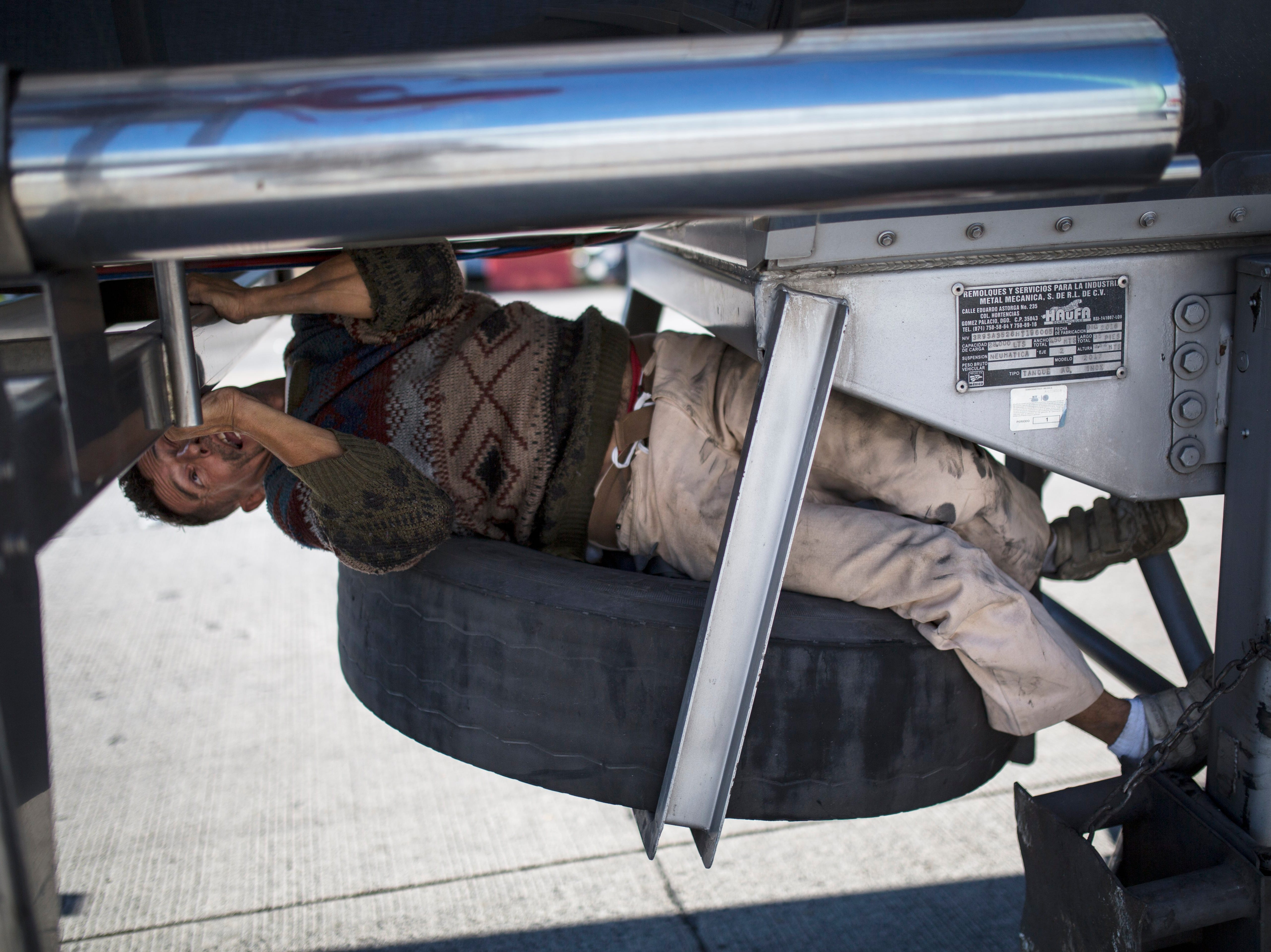 A Central American migrant tries to fit himself into a truck's spare wheel compartment, parked on the highway connecting Guadalajara and Tepic, Mexico, Tuesday, Nov. 13, 2018. Migrants thought buses would be waiting to take them through hurricane-ravaged Nayarit to the neighboring state of Sinaloa, further north, but no buses showed up and few trucks passed to pick them up, leaving many to walk.