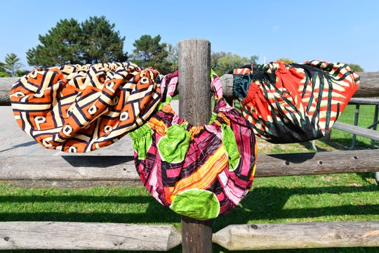 "Three handmade ""Life Hobo Bags"" made out of African prints from Mali by Kimberly Wilson of REA Alexander hang on a fence at Inglenook Park in Southfield."