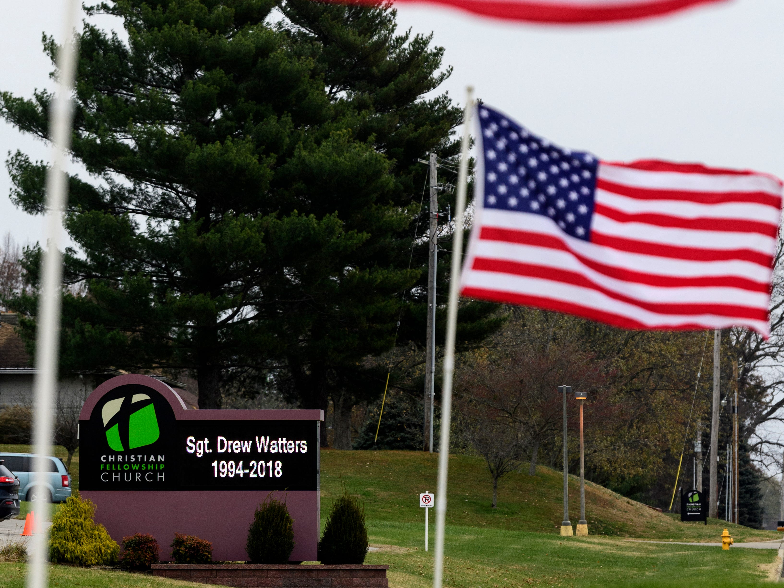 """Flags wave outside of Evansville's Christian Fellowship Church, where a visitation for U.S. Army Sgt. Drew Watters is held,Tuesday evening, Nov. 13, 2018. A """"Celebration of Life"""" ceremony, including military honors, will be held inside the church at 2 p.m. Wednesday, Nov. 14."""