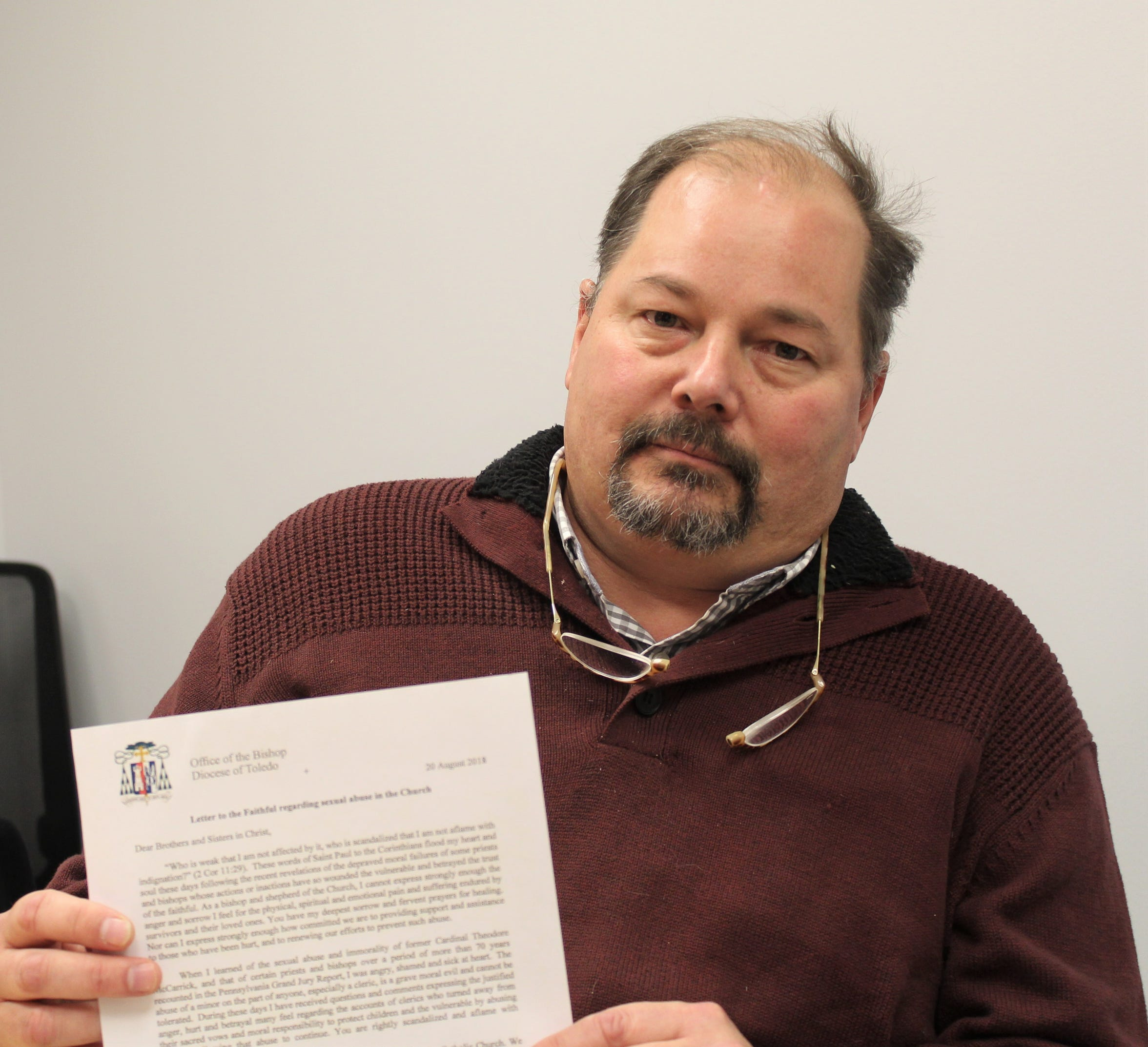 """Riley Kinn of Fostoria holds a """"letter to the faithful"""" from Toledo Bishop Daniel Thomas. Kinn has been requesting a meeting with the Catholic bishop to discuss allegations of sexual abuse by a Toledo priest when he was 13."""
