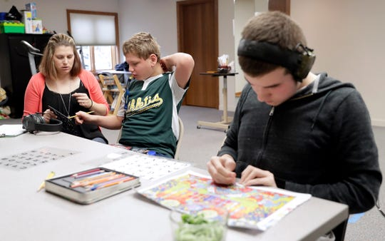 Isaac Bashta, 13, uses a letterboard held by ACE Teaching & Consulting co-owner and instructor Erika Anderson to communicate with his classmates, including Will Sheppard, 14, right, on Oct. 26 in Green Bay.