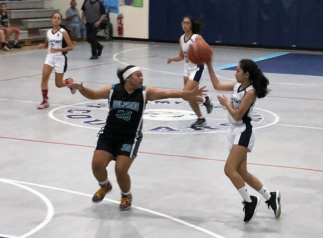 In this file photo from Nov. 7, Academy guard Mikaela Bumagat tosses a no-look pass in the Cougars big win over Southern High. Academy lost 47-43 to the Okkodo Bulldogs on Nov. 12.