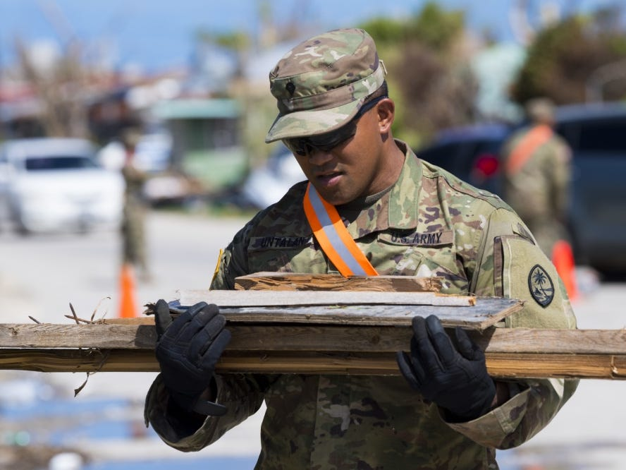 Guam Army National Guardsman Spc. Anselmo Untalan, 1224th Engineer Support Company engineer, carries wood during debris clean-up in the village of Chalan Kanoa, Saipan, Commonwealth of the Northern Mariana Islands, Nov. 9, 2018, as part of the Super Typhoon Yutu relief effort.