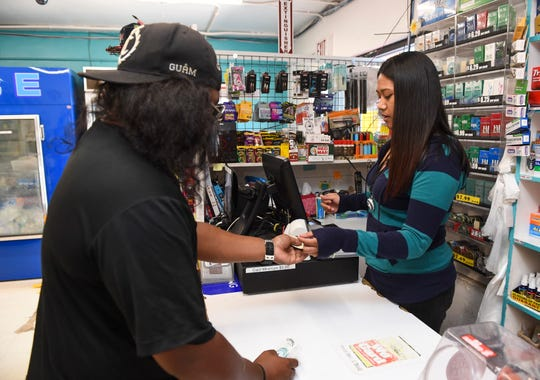 Cashier Stephanie Perez sells a pack of cigarettes to Ordot resident Jackson Skang at the Tutujan Quick Stop in Sinajana on Nov. 13, 2018.