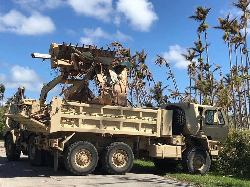 A Guam Army National Guard 1224th Engineer Support Company High Mobility Engineer Excavator (HMEE) loads a 10-Ton dump truck with debris on Chalan Kanoa, Saipan, today.