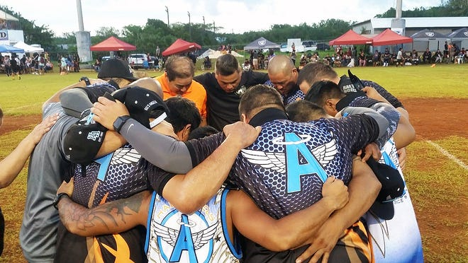 Hal's Angels coaches from all three divisions gather for prayer before the title games of the Guam National Youth Football Federation on Nov. 3.