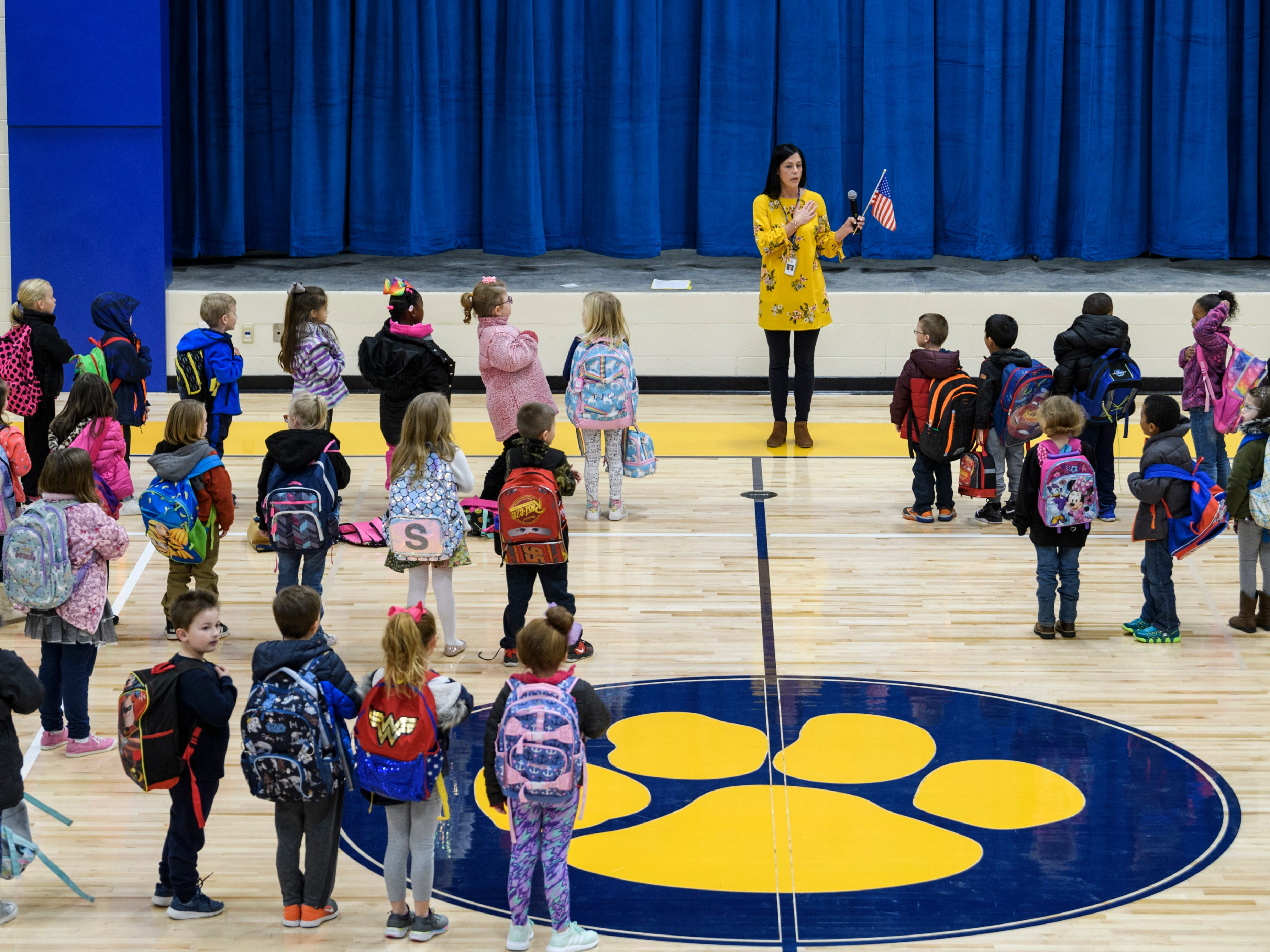 "Principal Sarah Estabrook, top center, leads the ""Pledge of Allegiance"" during the morning assembly inside the gymnasium at Spottsville Elementary school, Monday, Nov. 12, 2018. Monday was the first time that students had school inside the new $17 million, 76,796 square-foot facility."